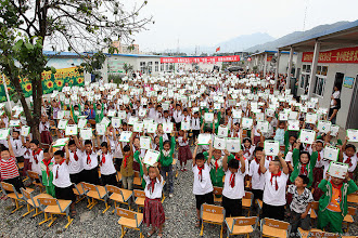 Photo: Students holding up XO laptops at school in Sichuan, China