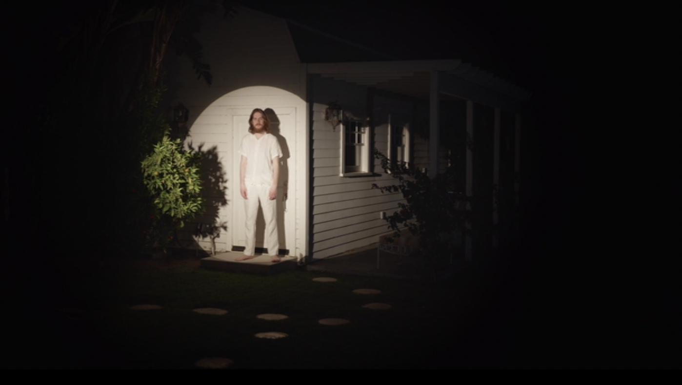 In front of his house, Burnham stands on a stage by himself, with a spotlight on him.