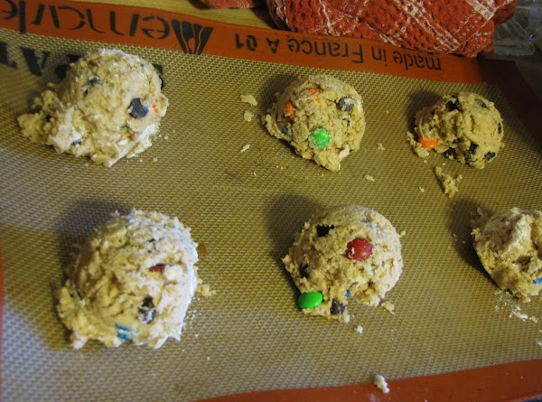 Using two lightly greased cookie sheet pans, place 6 ice cream scoops of dough...