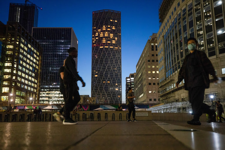 Pedestrians pass illuminated skyscraper offices in the Canary Wharf business, financial and shopping district of London, UK. Picture: BLOOMBERG/SIMON DAWSON