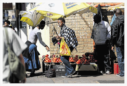 Shoppers and hawkers congregate outside a Shoprite store in Rosettenville, Johannesburg. The retailer has announced that it will prioritise job creation in the coming year