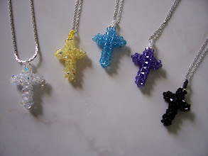 "Photo: Swarovski Crystal Cross. Size: 1"" x 1 3/4"" face and 3/8"" thickness with a 18"" chain. Color left to right: Clear AB, Jonquil AB, Sapphire light, Sapphire and Jet (black). $35.00 each."