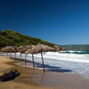 Row of straw umbrellas on a sand beach in Greece by Max Mayorov - Nature Up Close Water ( mountain, straw, travel, beach, landscape, sun, cover, sky, tree, parasol, water, sand, in a row, greek, beautiful, greece, scenics, umbrella, sea, traditional, vacations, row, destination, holiday, blue, wave, summer, view, welcoming )