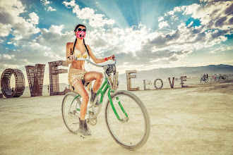 Photo: Love on a Bike  Here's one of the 65,000 people here at Burning Man.  Everyone rides bikes, wears costumes and facemasks, and ride around the desert seeing all kinds of interesting art. It's so surreal here, especially as the sun starts to go down when I took this photo.  I have a lot more photos coming soon... sorry if I overload you with stuff from the event for the next few weeks!