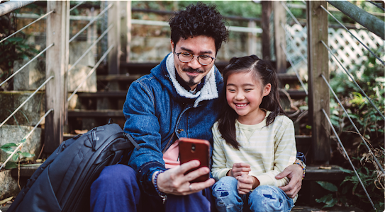 A father and daughter look at a phone together, smiling. They are sitting outside on steps.