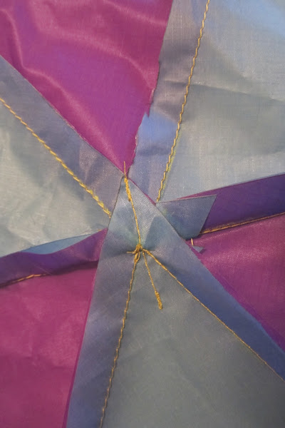 Photo: This is the second tip sewn down. The first stitch is hidden under the layers. Folded as flat as possible along the stitch line. Note this is forming a cone - so there is bunching in the other folds when flat on this axis. Seam is run out equidistant on either side just for a balanced look from the outside.