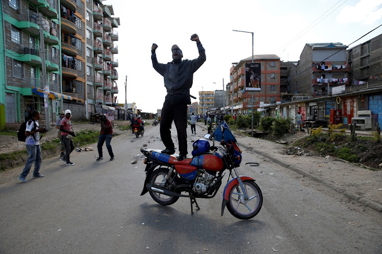 A supporter of Kenyan opposition National Super Alliance (NASA) gestures as he stands atop a motorbike in Nairobi, Kenya November 28, 2017.