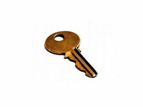Photo: Old worn brass key isolated on white