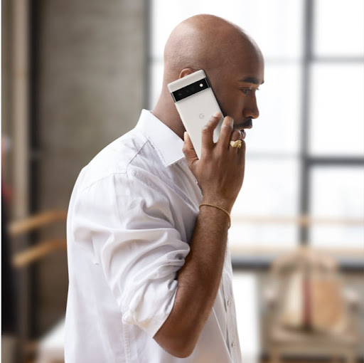 An image of a man talking on a Google phone.