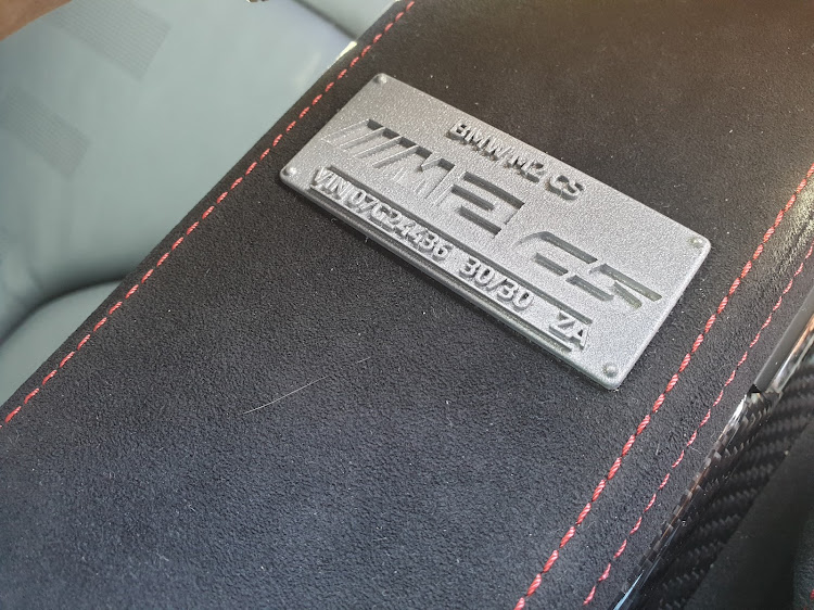 The numbered metal badge between the front seats identifies each M2 CS as part of a limited-edition series.