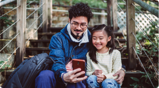 Father and his daughter looking at a mobile phone together