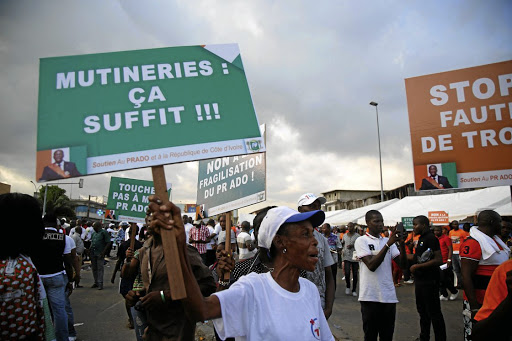 An Ivorian ruling party supporter holds a placard during a rally against a mutiny by soldiers close to the military headquarters in Abidjan, Ivory Coast, on May 13 2017. The placard reads,