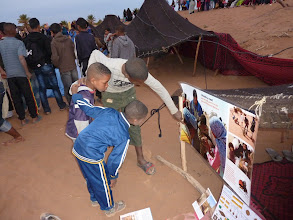 Photo: Local children recognise friends on the Sahara-Roots tree planting poster.