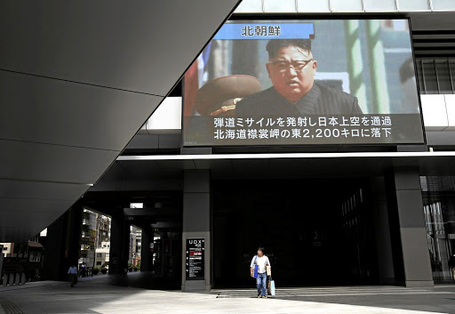 A passerby walks under a TV screen reporting news about North Korea's missile launch in Tokyo, Japan, on September 15 2017. Picture: REUTERS