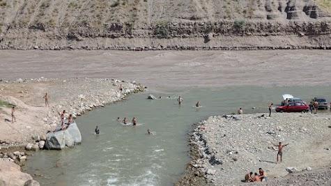 Tajiks bathe in a tributary of the Vakhsh.