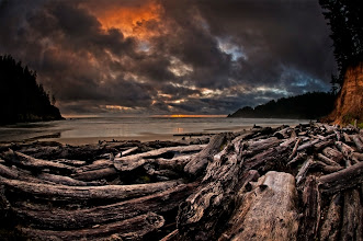 """Photo: Driftwood Graveyard  Saturday was a really good day, but it didn't start that way. I had plans to drive out to the coast to shoot some waterfalls and those plans changed the closer I got to the coast. It wasn't raining when I left the house but by the time I got to the parking lot for the first waterfall it was raining really hard. I decided to skip the falls and head down to Oswald West State Park to do somereminiscing about my childhood days when the family used to camp there. Today the campground has been closed and it's only open to day use but the beauty of that spot is still the same.  At the parking lot I gathered my gear and hit the trail. About 100 feet in the rain stopped. The closer I got to the beach the more light I could see in the sky and once I hit the beach I could actually see blue patches in the sky. Some say """"if you don't like the weather in Oregon, wait 5 minutes"""". Well that's not always the case, but I'm glad it was on this day.  I wandered the beach looking for the spot I would shoot sunset for and finally settled on a spot behind all the driftwood that has collected here over the years. I shot a few pictures and sat to enjoy the sunset, it was beautiful.  This is a two image blend done in +Adobe Photoshop, one exposing for the sky and one for the wood. A touch of style was given in +onOne Software's Perfect Effects.  #blog"""