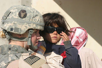 Photo: An Iraqi child tries on Spc. Taryn Emery's sunglasses during a humanitarian assistance mission in Qaryat Al Majarrah, Iraq, Nov. 27, 2006. Emery is with the 2nd Battalion, 136th Infantry Regiment.