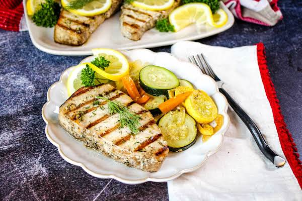 Grilled Swordfish On A Plate With Sauteed Squash And Zucchini.