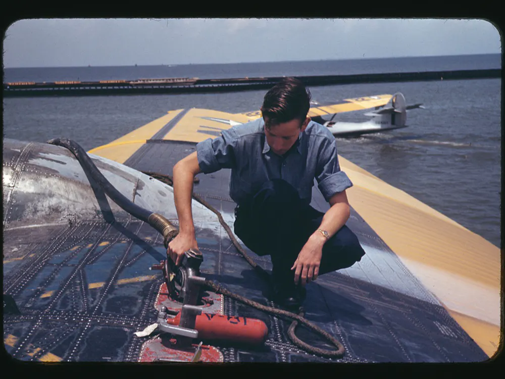 A person using a machine saw while wearing a chambray shirt