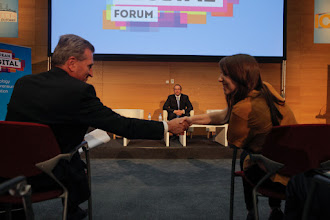 Photo: Günther Oettinger, European commissioner for digital economy and society, and Zoya Sheftalovich, technology reporter at Politico, shake hands. Rastislav Chovanec, state secretary of the ministry of economy of Slovakia, is on stage.