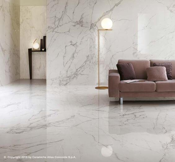 Sala com porcelanato reproduzindo mármore revestindo piso e paredes, sofá marrom e luminária de chão dourada