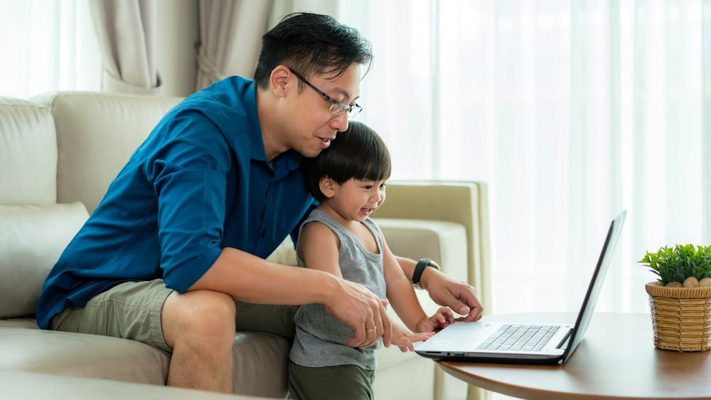 un hombre y un niño pequeño mirando un ordenador