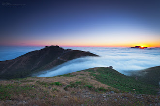 Photo: The last bit of the sun dips below the island of land in the sea of fog.