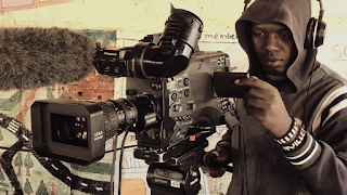 A young man stands behind a large video camera with multiple viewports and a boom microphone.