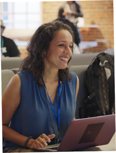 A woman working behind the laptop, smiling.