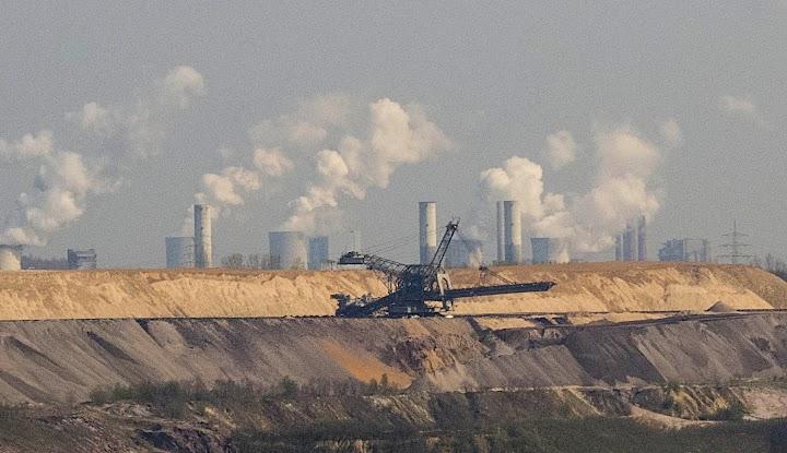 Braunkohlengrube, im Hintergrund qualmende Industrie-Schornsteine.