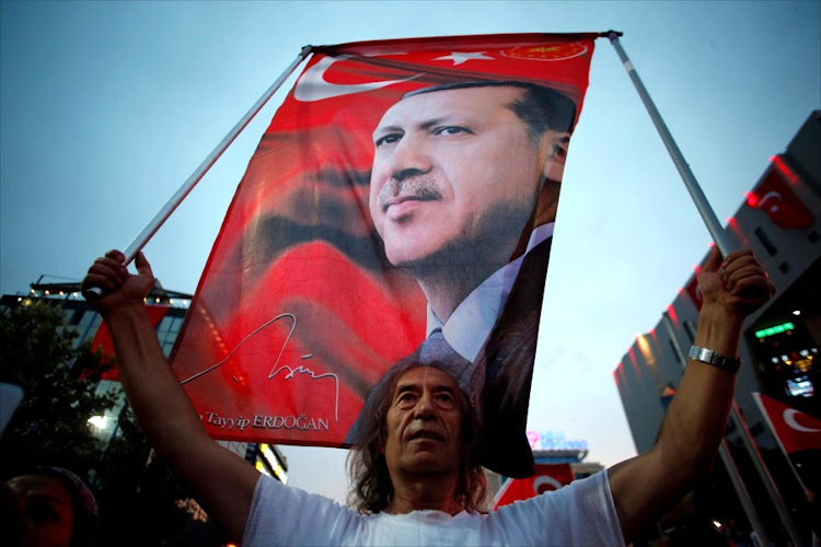 A supporter holds a flag depicting Turkish President Recep Tayyip Erdogan. Picture: REUTERS/BAZ RATNER
