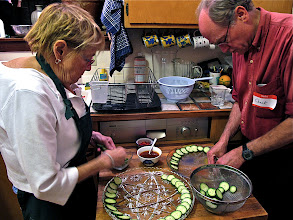 Photo: Kathy and Chuck arranging sliced cucumber on serving platters for the toasts
