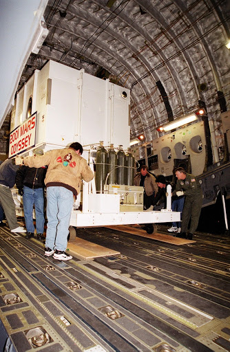 The Mars Odyssey spacecraft is maneuvered for removal from the Air Force C-17 cargo airplane that brought it from Denver.