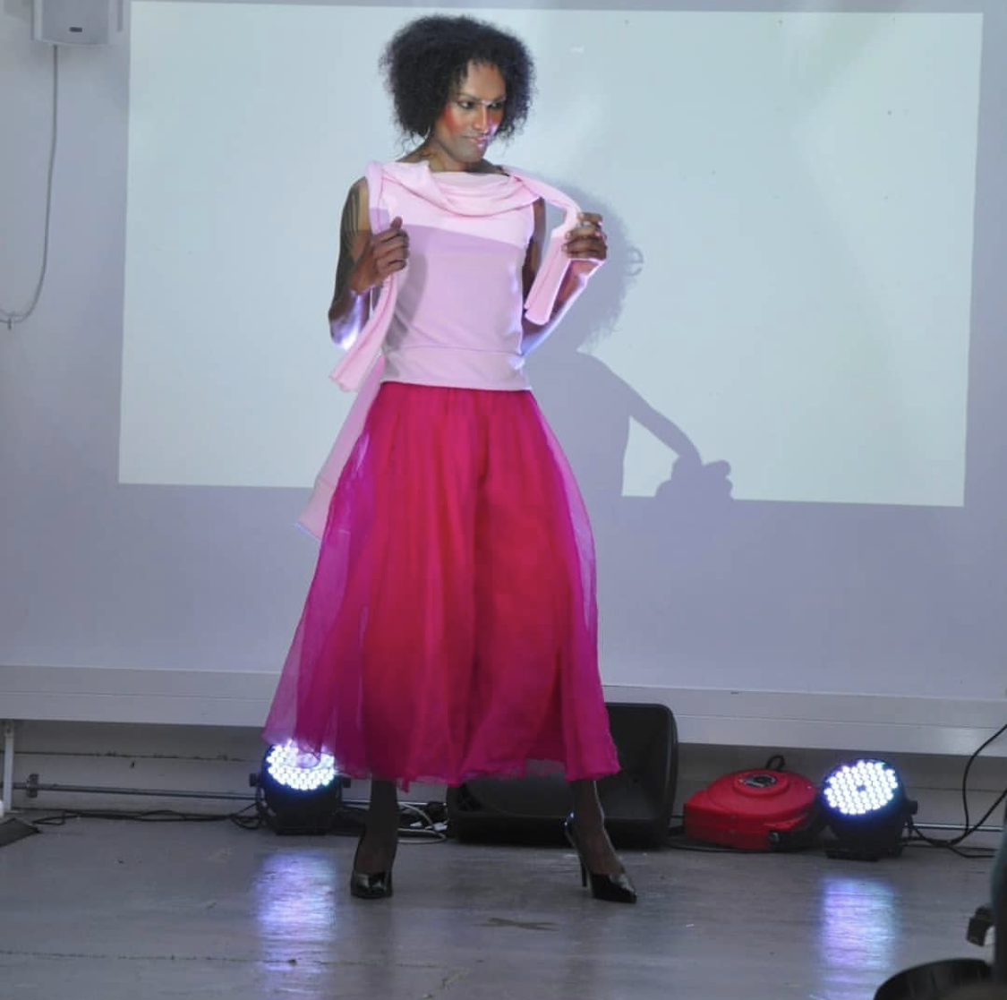 Photograph of me on the catwalk with heavy blusher and afro hair. I am wearing a short sleeved light pink top and pleated wide legged cropped magenta organza trousers