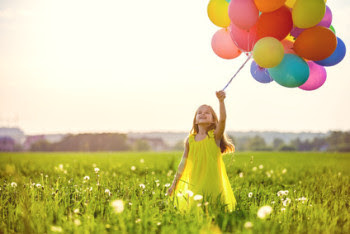 Six year old girl in field holding balloons