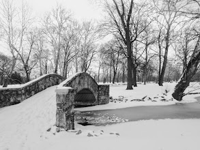 Photo: Black and white photo of a stone bridge with snow over an ice lake at Eastwood Park in Dayton, Ohio.