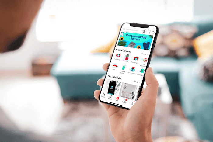 """Individual holds mobile phone which at top displays """"Recommended seller"""" and below that """"Explore Carousell"""" with a serices of icons and """"Your daily pics"""" with a series of photos"""
