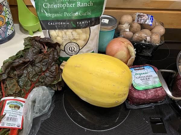 Ingredients Spread Out: Swiss Chard, Garlic, Spaghetti Squash, Onion, Plain Yogurt, Mushrooms, And Ground Beef.