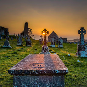 Sunset through the cross by F Kelly - City,  Street & Park  Cemeteries ( high cross, ireland, monastery, celtic cross, offaly, clonmacnoise, river shannon, graveyard )