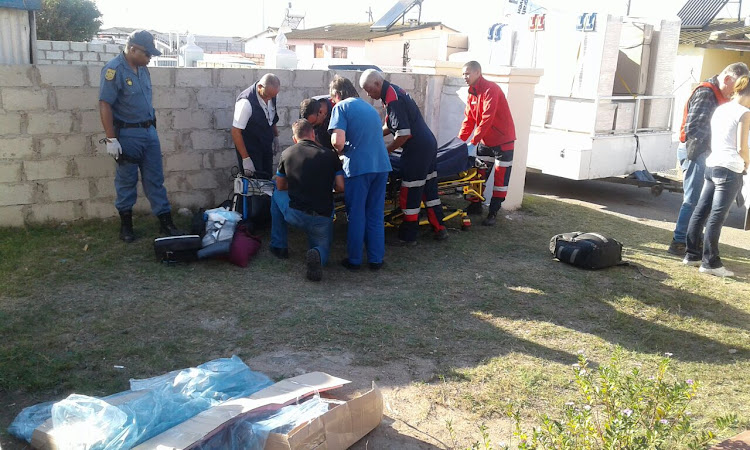 Medics treat a man who was shot four times during a suspected botched robbery