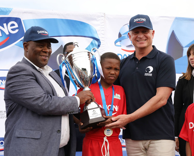 "SASFA chairman Mandla ""Shoes"" Mazibuko with the captain of the winning team and Hendrick Born, managing director of Danone Southern Africa"