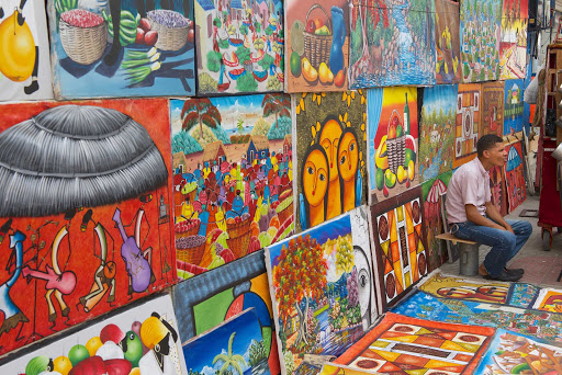 Cuban-Street-Art-and-Sitting-Man.jpg - Artists ply their wares at a market in Cuba.