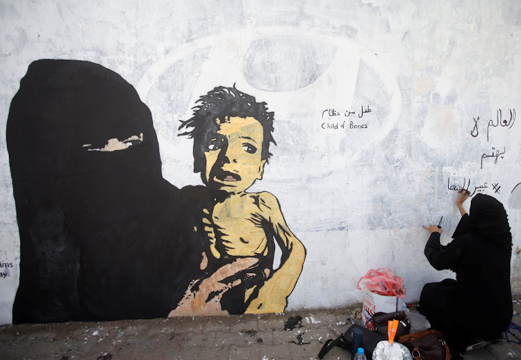 A friend of artist Haifa Subay writes on a mural about children and women suffering in Sanaa, Yemen.