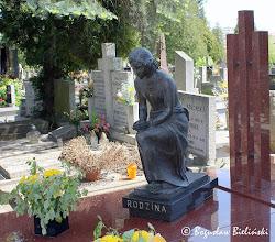 Photo: Do najbardziej sugestywnie przemawiających i przeważnie najciekawszych nagrobków na każdym cmentarzu należą nagrobki figuralne. Na łódzkim Cmentarzu Katolickim św. Franciszka reprezentuje je między innymi, pomnik nad grobem rodziny Muszyńskich. Pomnik ma formę prostopadłościennego grobowca z polerowanego, brunatno-czerwonego granitu z trzema słupkami umieszczonymi w lewym narożu, natomiast głównym jego motywem zdobniczym, jest wykonany z brązu naturalnej wielkości posąg młodej dziewczyny, klęczącej na cokole, z dłońmi złożonymi w modlitewnym geście.