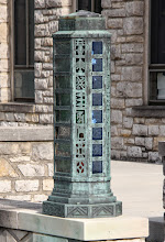 Photo: Brass lamps adorn the steps leading to the north doors. Aging has created the verdigris run from the lamp to the relief below. This additional embellishment of aging brass can be seen in the tower cap and base as well.