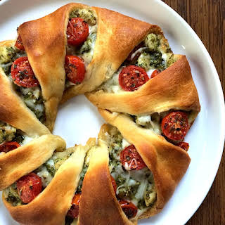 Cheesy Pesto Chicken Crescent Roll Wreath with Roasted Cherry Tomatoes.