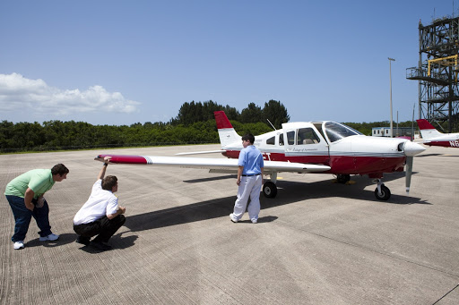 A flight instructor and his students inspect the lightweight aircraft they flew or FIT in Melbourne.