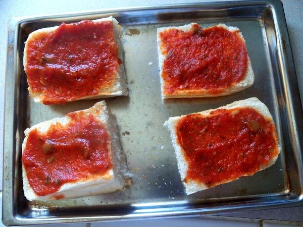 Warm toaster oven to 350 degrees. Slice sandwich roll, spread with 1 tbsp desired...