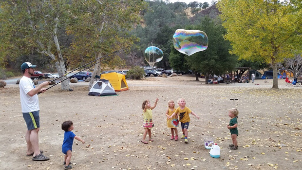 Man making giant bubbles for five toddlers at a camp site