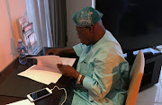 Olusegun Obasanjo, former Nigerian president and chairman of the West Africa Commission on Drugs,  looks at documents during an interview in Dakar, Senegal, on September 11 2018.
